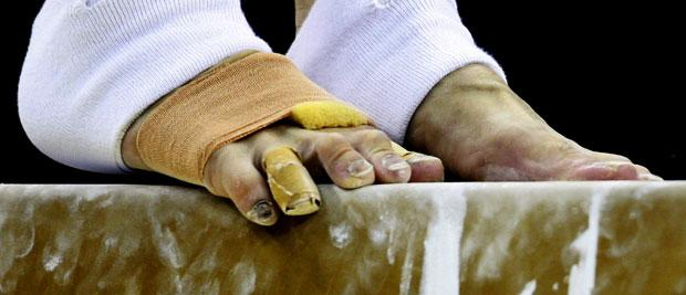 Z13 gymnast with damaged toes practices on the beam